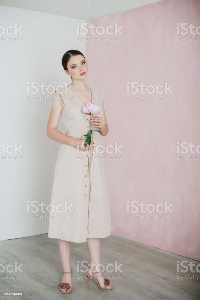 A young woman with gathered hair is standing holding a peony in her hands royalty-free stock photo