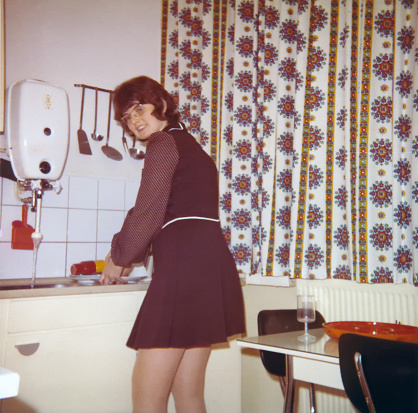 Vintage 1972 image of a young woman with mini skirt doing the dishes in the kitchen.