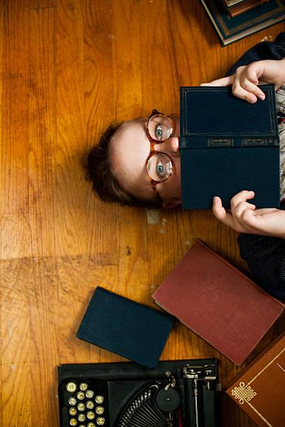 junge frau mit brille verstecken hinter buchen - kurzgeschichten stock-fotos und bilder