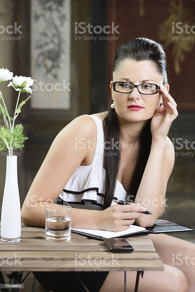 Young Woman with glasses sitting at the table royalty-free stock photo