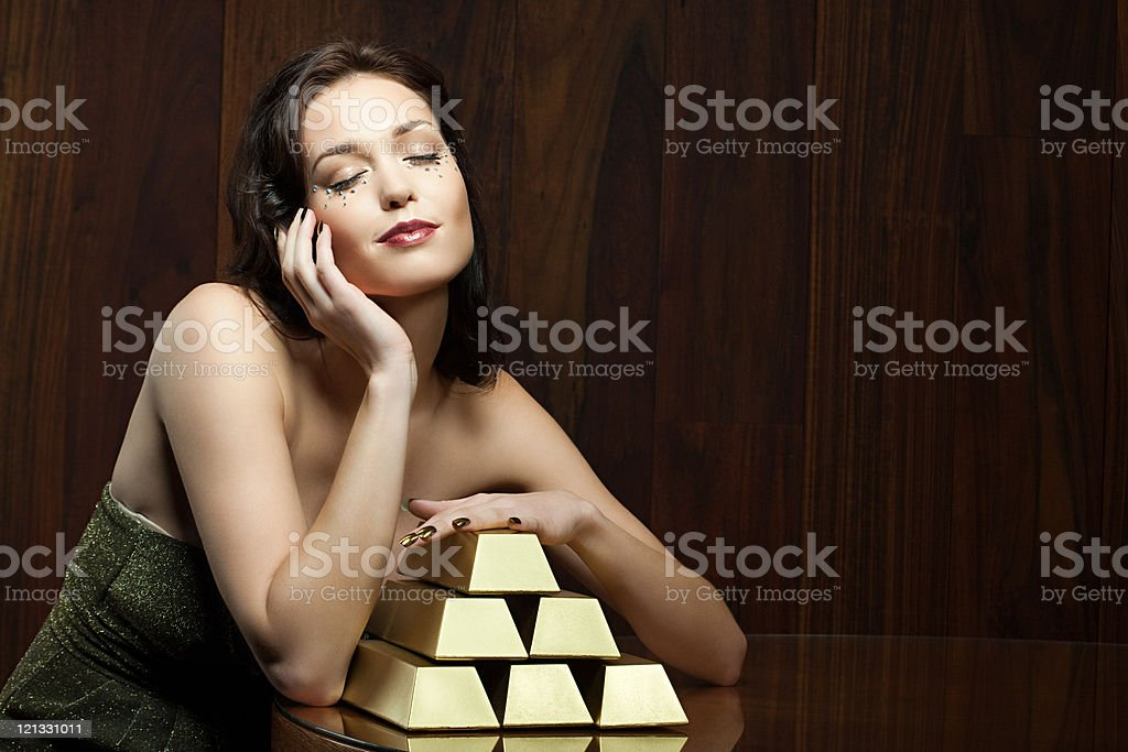 Young woman with gold ingots stock photo