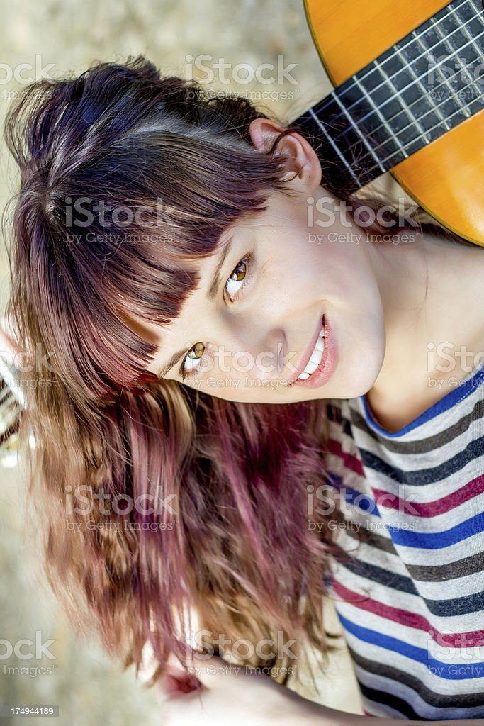 Young woman with guitar smiling, looking at camera, posing outdoors. royalty-free stock photo