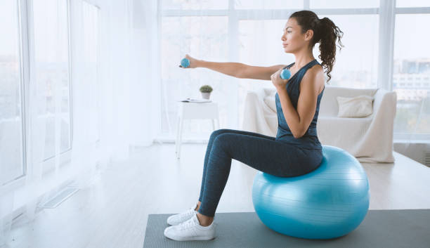 Young woman with gym ball and dumbbells at home, blank space stock photo