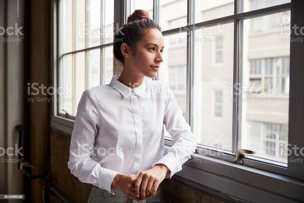 Junge Frau mit Haar Bun Blick aus Fenster, Hüfte aufwärts – Foto