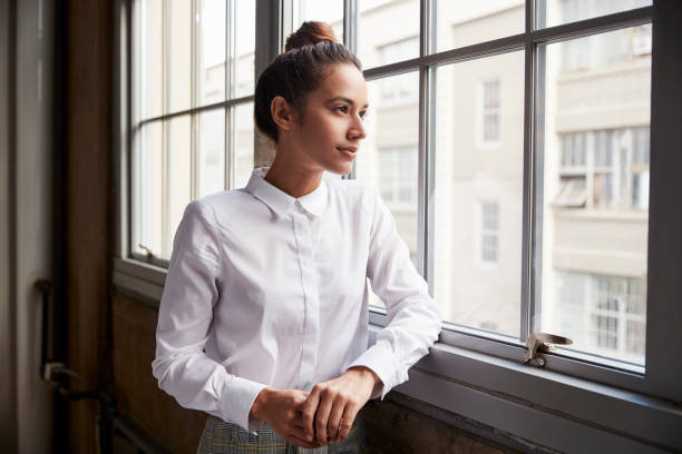 Young woman with hair bun looking out of window, waist up Young woman with hair bun looking out of window, waist up blouse stock pictures, royalty-free photos & images
