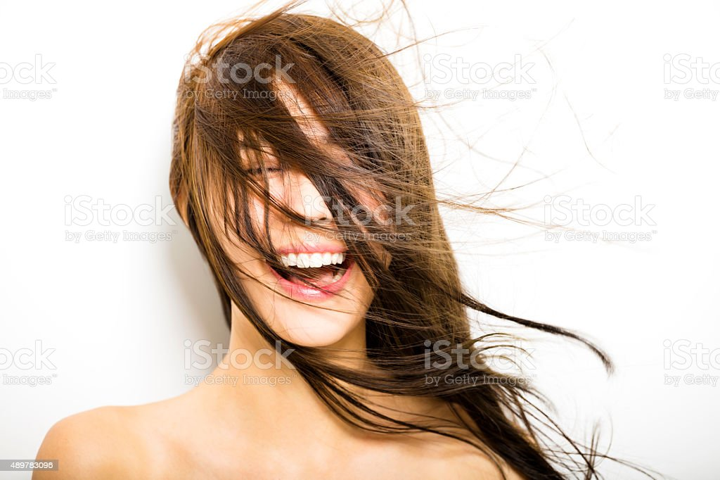 Giovane donna con i capelli in movimento su sfondo bianco - foto stock