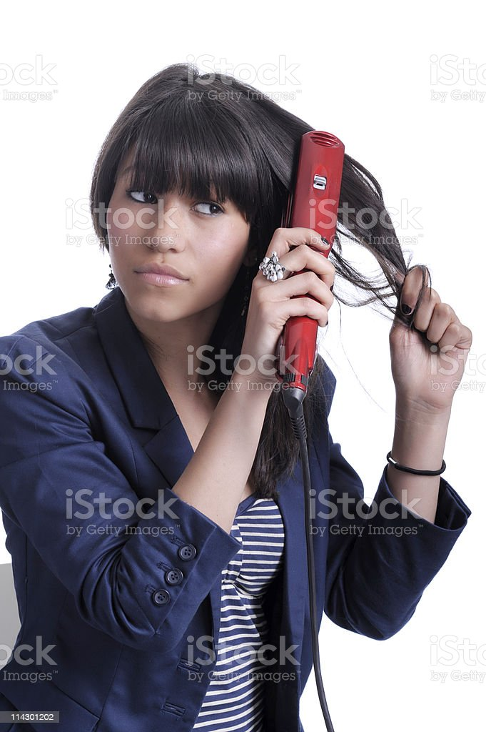 young woman with hair straightener royalty-free stock photo