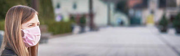 Young woman with hand made face nose mouth mask portrait, blurred empty city square behind her. Wide banner space for text - can be used during coronavirus covid19 outbreak prevention stock photo