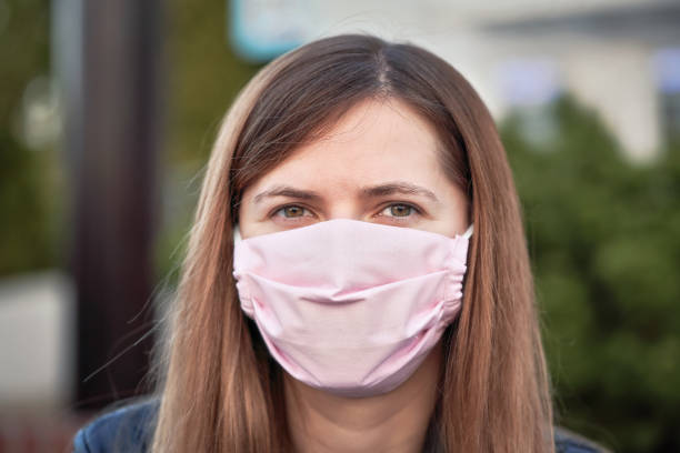 Young woman with hand made face nose mouth mask portrait, can be used during coronavirus covid19 outbreak prevention stock photo