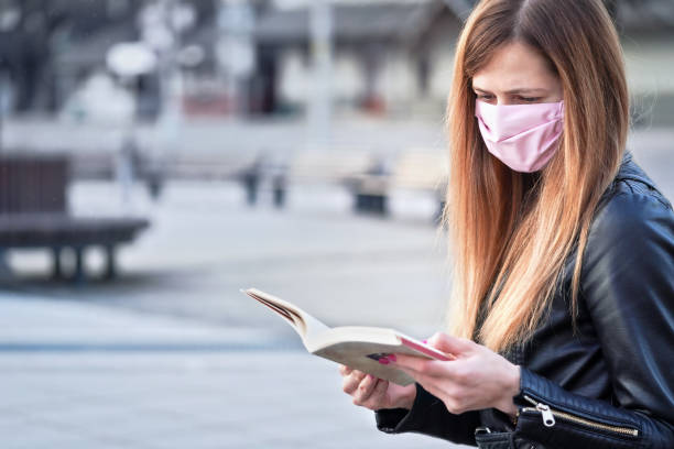 Young woman with hand made pink face nose mouth mask sitting alone, reading book, empty city square behind her. Can be used during coronavirus covid19 virus otbreak stock photo
