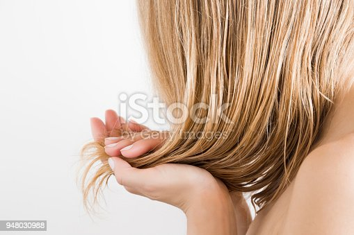 istock Young woman with hand touching her wet, blonde, perfect hair after shower on the white background. Care about beautiful, healthy and clean hair. Beauty salon concept. Side view. 948030988
