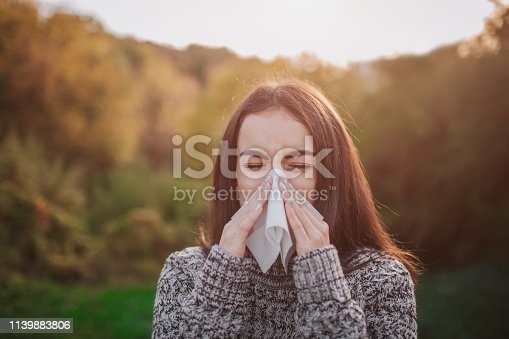 young woman with handkerchief. Sick girl has runny nose. Female model makes a cure for the common cold on an autumn background.