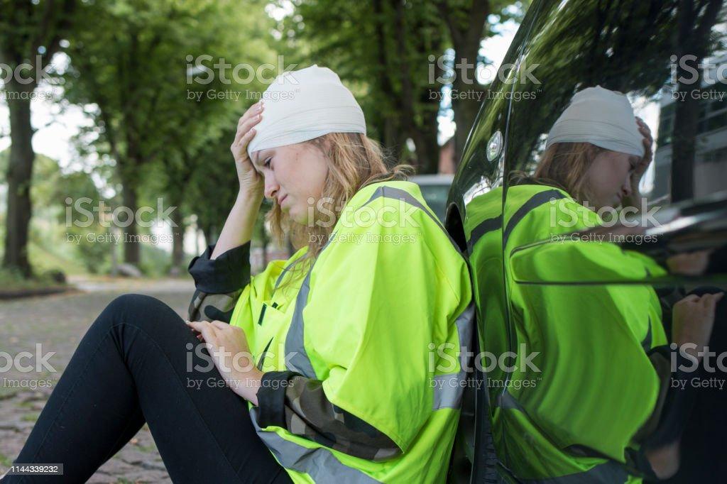 Eine junge Frau mit Verband am Kopf sitzt auf der Strasse und lehnt...