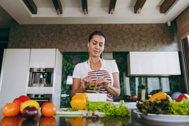 Young woman with headphones in the ears holding vegetables in hands in kitchen with laptop on the table. Vegetable salad. Dieting concept. Healthy lifestyle. Cooking at home. Prepare food stock photo