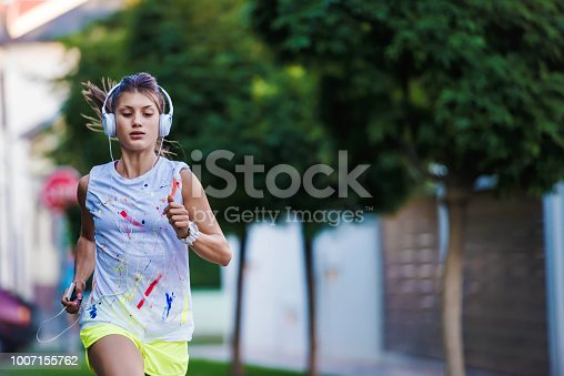 Urban sporty girl with headphones jogging in suburb