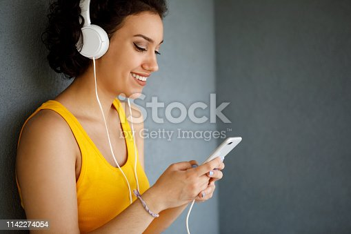 Young woman with headphones texting on the phone