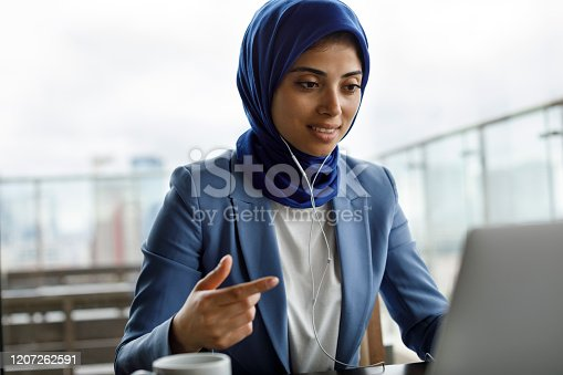 Young woman with headphones working on laptop