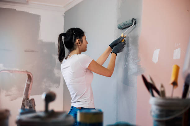 Young woman with hearing aid painting walls stock photo