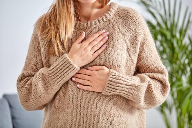 mujer joven con corazón problema holding en el pecho. - pecho torso fotografías e imágenes de stock