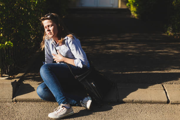 Young woman with heart problems feeling sick outdoors stock photo