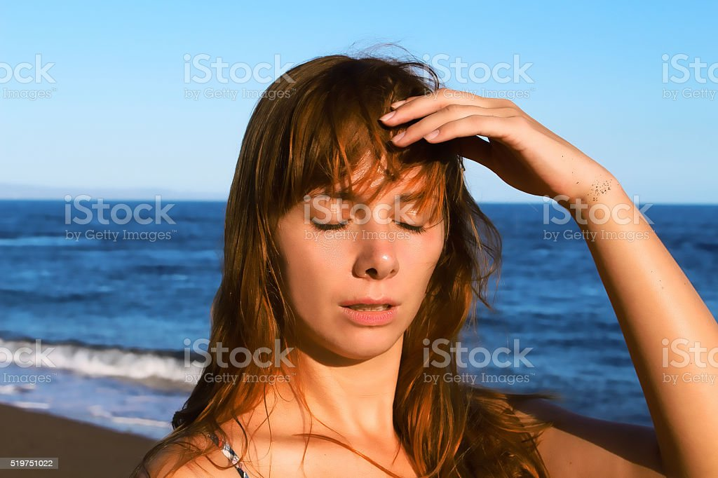 Young woman with heatstroke, sunstroke  on a beach stock photo