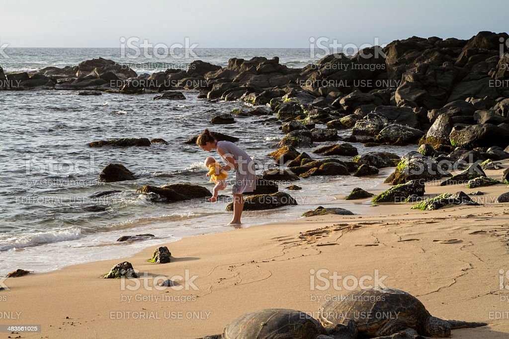 Young woman with her baby at turtle beach stock photo