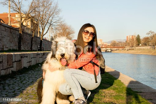 Young woman with her dog together near river. Pet care