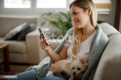 483426960istockphoto Young woman with her dog using mobile phone at home 1138653542