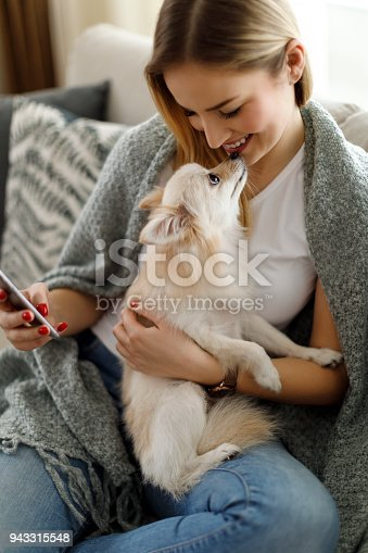 483426960istockphoto Young woman with her dog using mobile phone at home 943315548