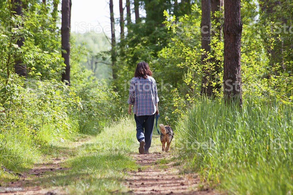Young woman with her dog walking in the wood royalty-free stock photo