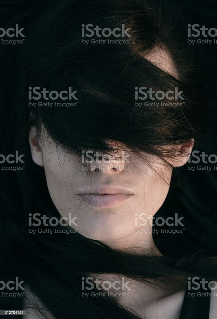 Young woman with her hair across her eyes stock photo