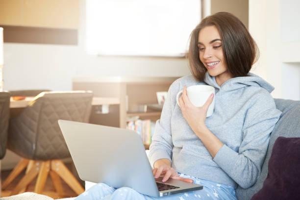 Junge Frau mit ihrem Laptop auf Sofa zu Hause sitzen und Tee trinken – Foto