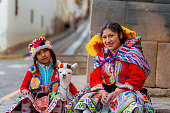 istock Young woman with her little niece pose in a portrait with their typical costumes next to her little alpaca in a street in the historic center of Cusco 965712768
