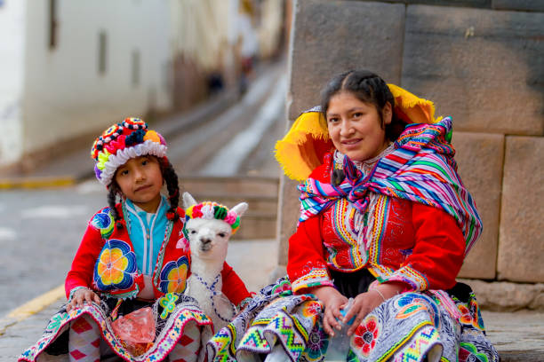 Young woman with her little niece pose in a portrait with their typical costumes next to her little alpaca in a street in the historic center of Cusco Cusco, Peru - February 10, 2018: Young woman with her little niece pose in a portrait with their typical costumes next to her little alpaca in a street in the historic center of Cusco peruvian culture stock pictures, royalty-free photos & images
