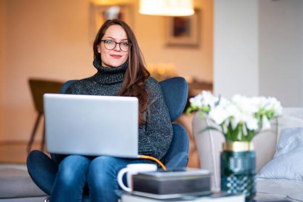 Junge Frau mit ihrem Notizbuch auf dem Stuhl im Wohnzimmer sitzend – Foto