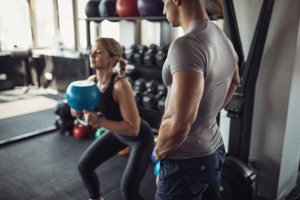 jonge vrouw met haar personal trainer in de sportschool - personal trainer stockfoto's en -beelden