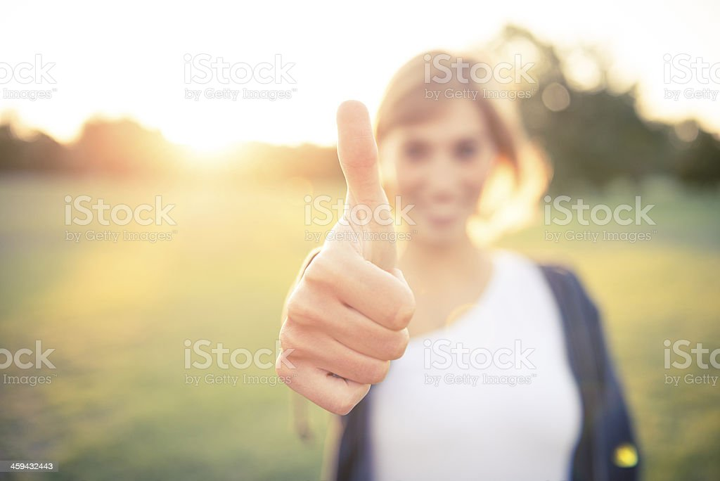 A young woman with her thumb up outside stock photo