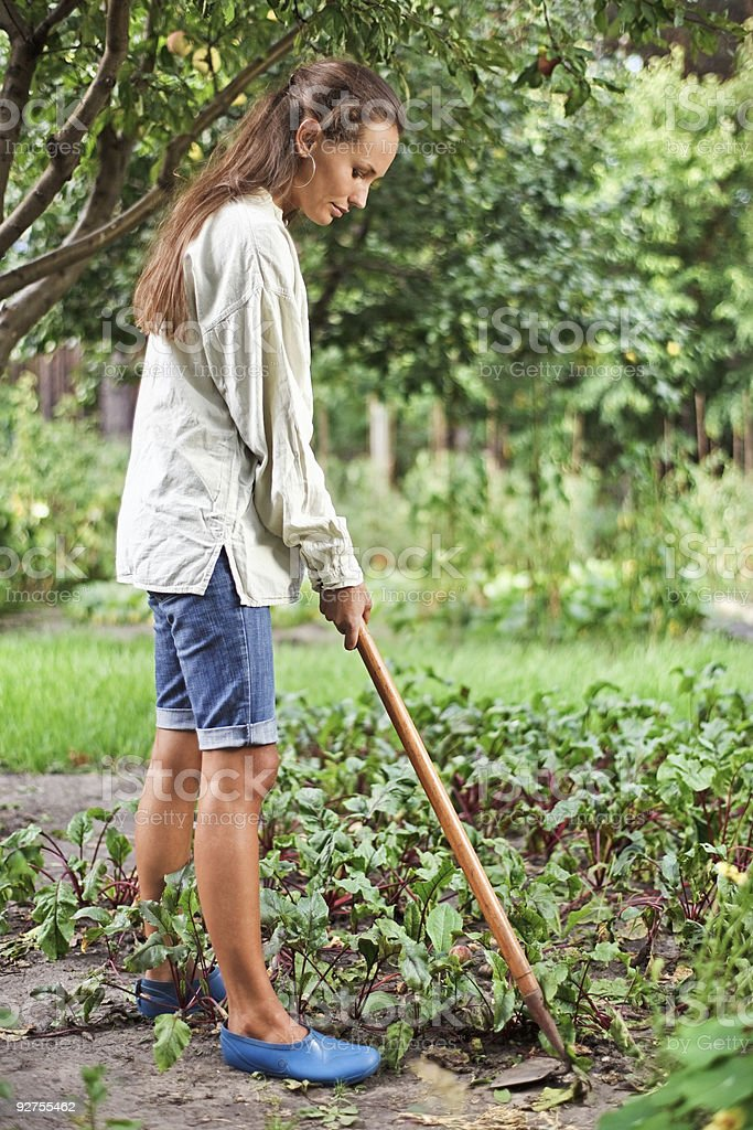 Young woman with hoe working in the garden bed stock photo