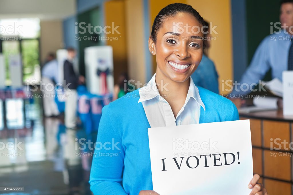 Young woman with I Voted sign at voting election center royalty-free stock photo