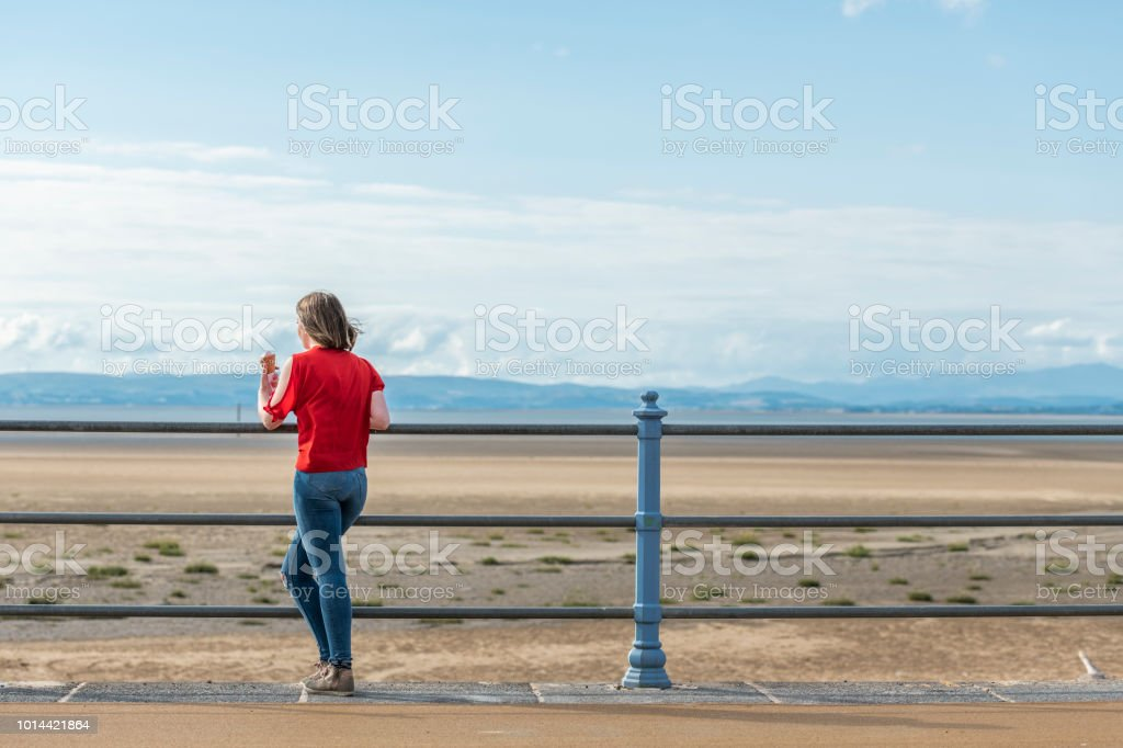 Young Woman with ice-cream at Morecambe Bay, Northwest England stock photo