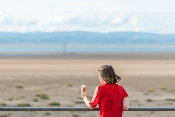 young woman with ice-cream at morecambe bay, northwest england - ice cream cone stock photos and pictures