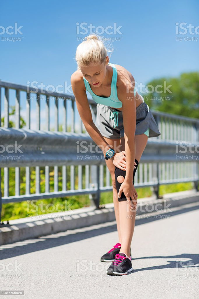 young woman with injured knee or leg outdoors stock photo