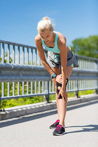 young woman with injured knee or leg outdoors - human knee stock photos and pictures