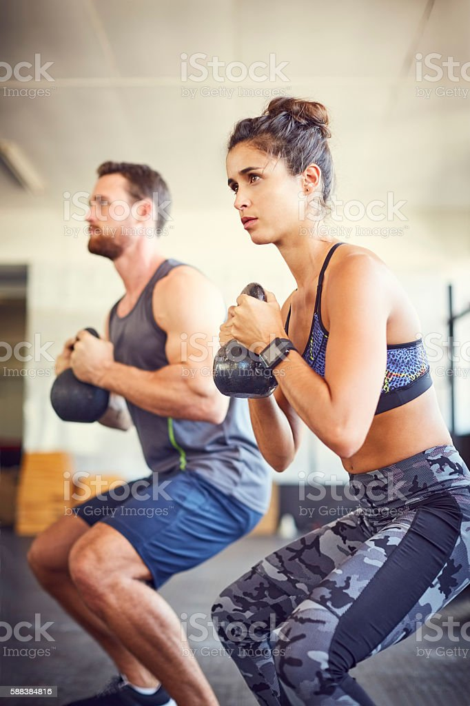 Young woman with instructor lifting kettlebells in gym stock photo