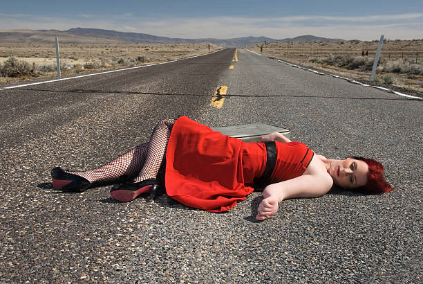 Young woman with is laying lifelessly  on highway stock photo