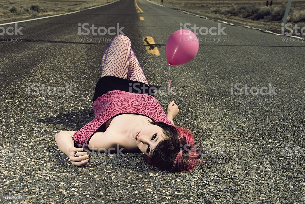 Young woman with is laying on the road holding balloon stock photo