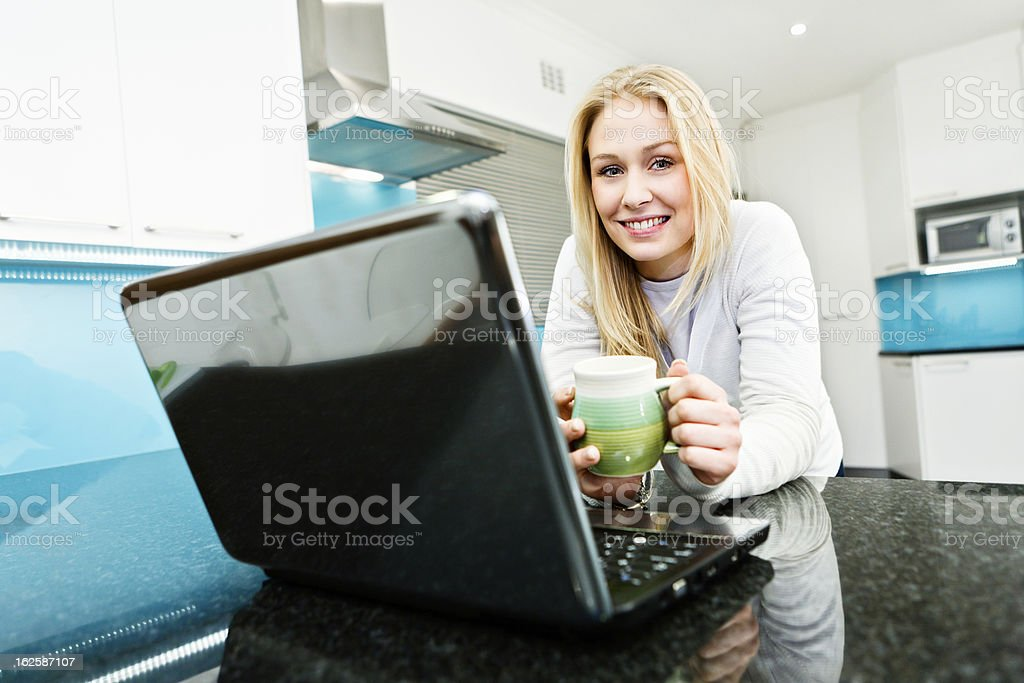 Young woman with laptop and coffee mug in modern kitchen royalty-free stock photo