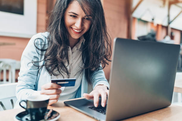 Young woman with laptop and credit card in cafe stock photo