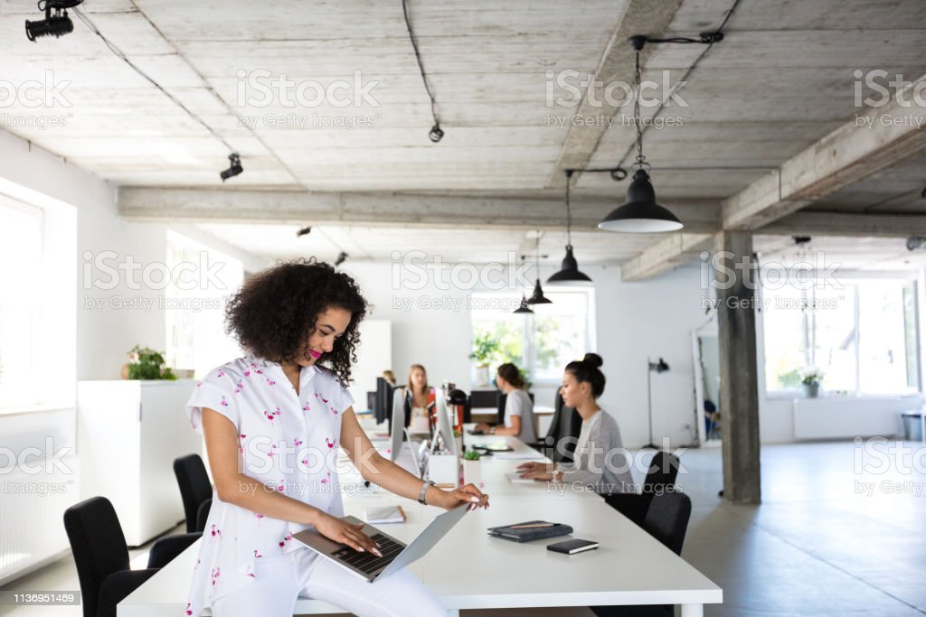 Young woman with laptop at office Young woman with laptop sitting at the table with coworkers working on computers in background. 20-24 Years Stock Photo