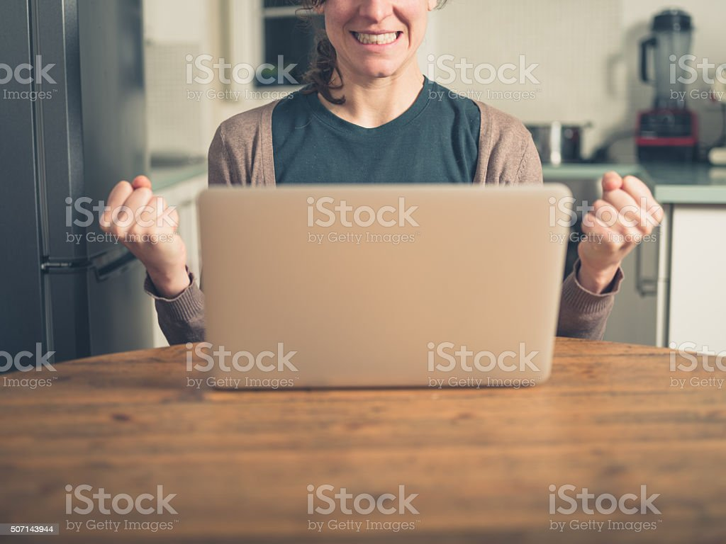 Young woman with laptop fist pumping in kitchen stock photo